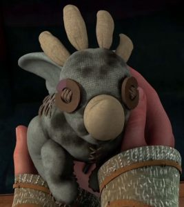 Hiccup holding his childhood toy that his mother had made for him when he was a baby.