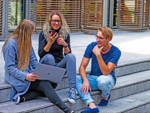 friends sitting on concrete steps, cheerful, using laptop