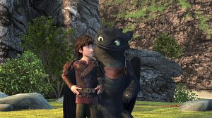 Hiccup and Toothless both standing on 2 feet and looking at each other.