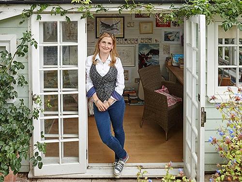 Cressida Cowell standing in doorway to her garden shed